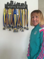 Kathy Waldron stands next to a wall display in her