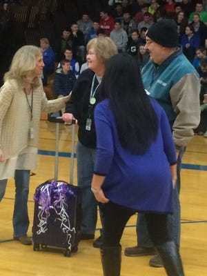 Staff members Joan Birder Gilliam, left, and Ying-Jing Vang, foreground, congratulate Terry Ellis, middle, as she's honored at the end of Green Bay Southwest High School's second annual DUDE. be nice Week in the school gym Friday. Ellis was joined by her husband, Tim, right.
