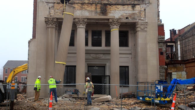 Miron construction employees remove the stone pillars from a historic bank building on Main St. on Dec. 23 in Menasha.