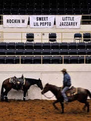 A rider trots past a horse tied to the Coliseum railing