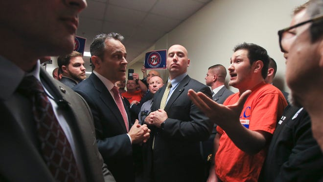 In a crowded Capitol Annex hallway filled with union workers, Kentucky Governor Matt Bevin listens Wednesday as Tim Morris, representative from the Greater Louisville Labor Council, argued against Bevin's support for Right-to-Work legislation.