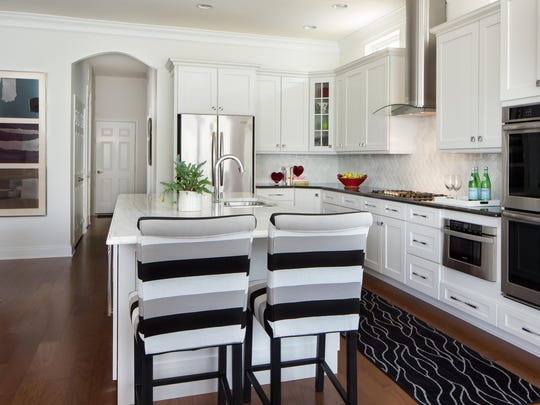 A white marble countertop was used on this large, double-width 10-foot island to enhance the soft and subtle aura of this open floor plan. The black granite countertops at the perimeter of the room add definition and contrast to this crisp, classic look. The counter stools with metal legs and durable fabric in bold horizontal stripes add softness and interest to the kitchen.
