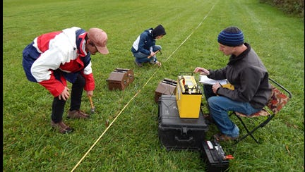 Eric Armstrong, right, operates a SuperSting resistivity meter while doing geology research.