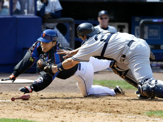 Yankees catcher Jorge Posada, right, trying to apply the tag as Mets pitcher Dae-Sung Koo scores during the game at Shea Stadium on May 21, 2005.