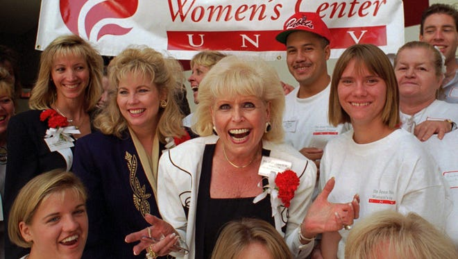 Jean Nidetch, center, founder of Weight Watchers International,  reacts with a group of workers from the Jean Nidetch Women's Center during a Jobs Fair on the campus of the University of Nevada at Las Vegas in Las Vegas. Nidetch, a New York housewife who tackled her own obesity problem, then shared her guiding principles with others in meetings that became known as Weight Watchers, the most widely known company of its kind, died Wednesday April 29, 2015, at her home near Fort Lauderdale, Fla., her son David Nidetch said. She was 91. (AP Photo/Lennox McLendon, File)