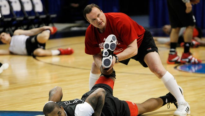 Louisville strength coach Ray Ganong, top, helps guard Chris Smith stretch during practice at the Pepsi Center in Denver on Wednesday, March 16, 2011.  They are getting ready for their southwest regional NCAA college basketball tournament second round game against Morehead State on Thursday. (AP Photo/ Ed Andrieski)