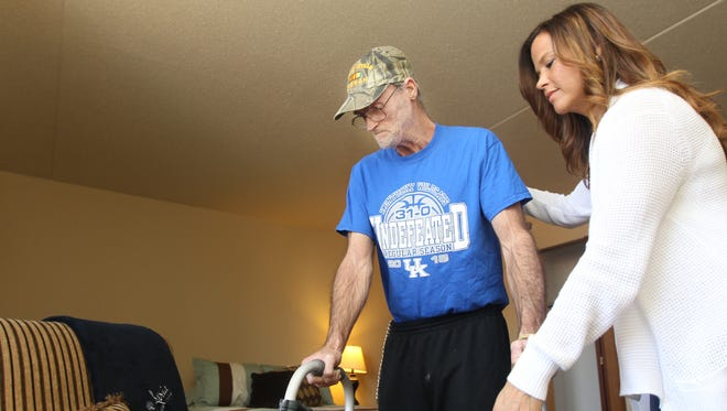 Michelle McKenney, of Hebron, helps her father, Eugene McKenney, to a chair in his room at Atria Highland Crossing, Fort Wright. McKenney, 63, a Vietnam War veteran who was homeless and went to the Elsmere Police Department and asked to be arrested for vagrancy so he could get shelter. Several social service agencies and family members have worked to get him help and shelter.