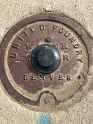 A steel plate set in concrete marks where a water meter