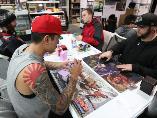 "Randy Kennedy, left, Nick Griffin, Jack Martin and Justin Perkins play the trading card game ""Magic: The Gathering"" on Wednesday, Dec. 23, 2015, at Wild Things Games in downtown Salem, Ore."