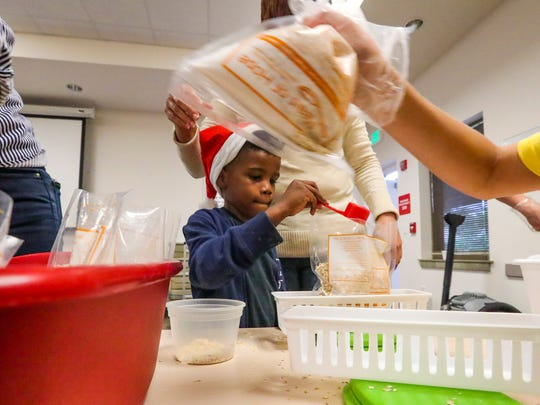 Five-year-old Taj Anderson works to weigh the packets as he volunteers with his family. These food packets will be distributed to United Way houses and other partnering agencies that help people who are still recovering financially from Hurricane Irma.