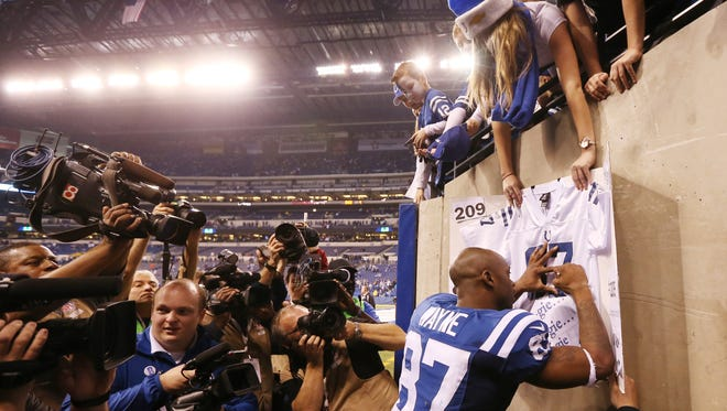 All the cameras were on Colts wide receiver Reggie Wayne as he signs an autograph for fans following a big win over the Texans.