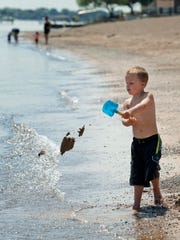 J.P. Russel, 4, of Macomb Township, throws sand with a shovel while playing Thursday at Lakeside Park in Port Huron. The first phase of renovations at the park starts in September.
