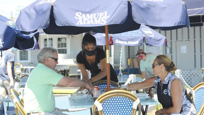 Bruna DaSilva, a runner at Spanky's Clam Shack in Hyannis, serves lunch to Mark Early and Francine Ryan outdoors at the restaurant Monday afternoon. The restaurant has only 10 outdoor tables that can accommodate about 40 people, but co-owner Billy Moore said business was brisk.