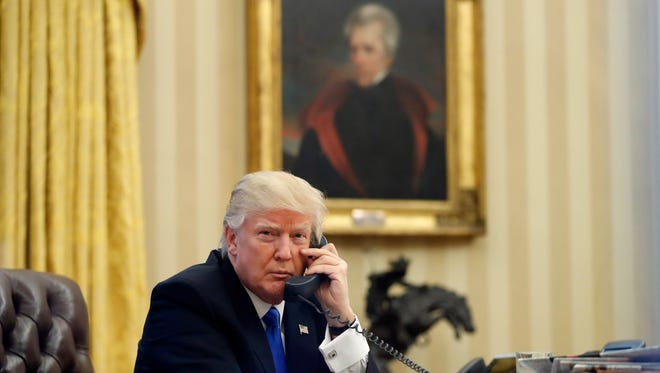 President Donald Trump sits near a portrait of Andrew Jackson in the Oval Office.