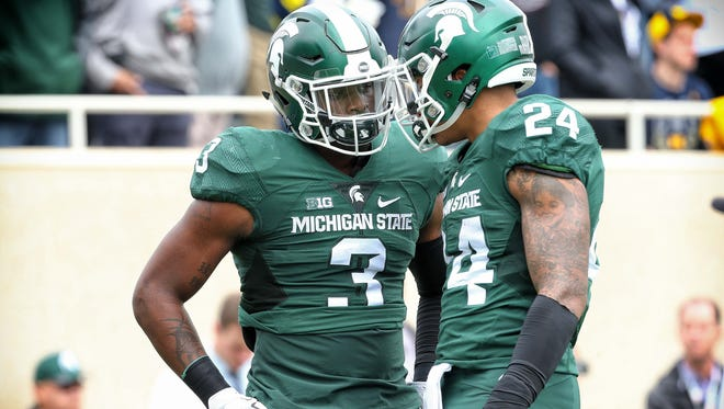 MSU running back's Gerald Holmes, right, and LJ Scott, left, are going to be counted on to lead the Spartans this fall. Holmes has taken it upon himself to be an encouraging presence.