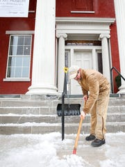Gregg Leavenworth, facilities manager, chips and scrapes ice from the steps of the Arnot Art Museum on Lake Street in Elmira on Tuesday morning.