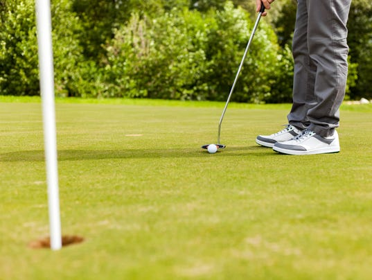 Male golf player drivers ball into the hole