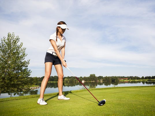 Golf player preparing for teeing off.