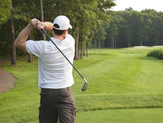 Young male golfer tees off on a par three