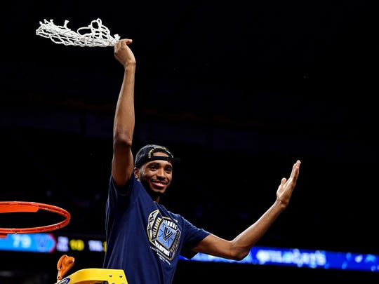 Mikal Bridges celebrates with the net after beating