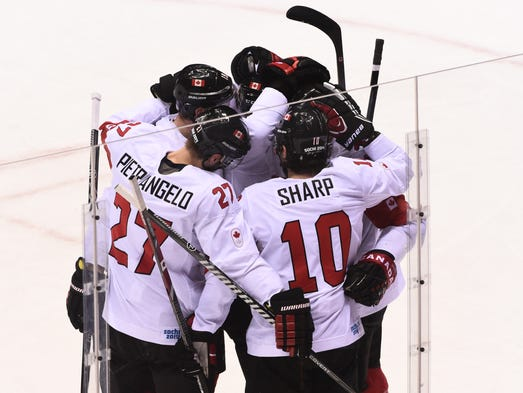The Canadian team huddles after a score against Latvia in the men's ice hockey quarterfinals.