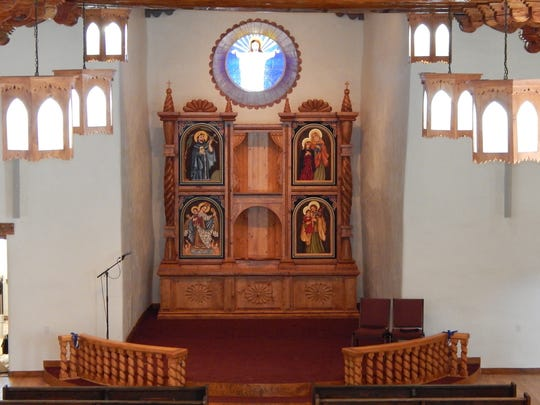In this Thursday, Aug. 11, 2016, photo, provided by Carrie Leven, shows the installation of the retablos, or devotional paintings, at the alter of the reconstructed San Antonio Catholic Church are part of the finishing touches being made in Questa, N.M. The community will celebrate the rededication of the church with a special Mass on Sunday, Aug. 14, 2016.
