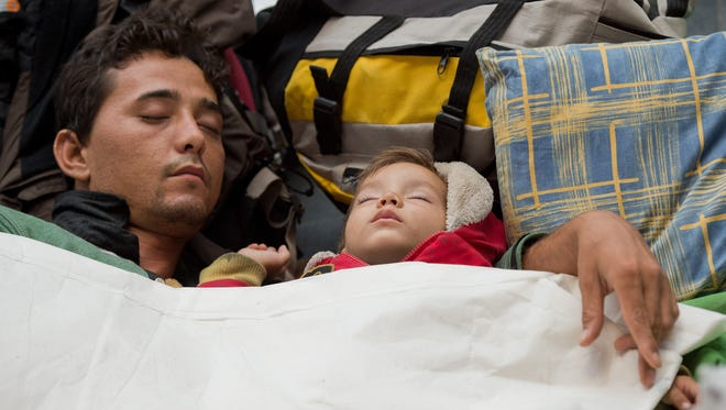 A man and a child sleep Sept. 14, 2015, at the main railway station in Frankfurt am Main, Germany, where refugees from Syria, Iraq and Pakistan arrived during the night on a train from Austria.