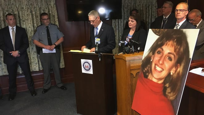 FILE - In this Monday, June 25, 2018 file photo, Lancaster County District Attorney Craig Stedman announces charges in a 1992 cold case killing during a news conference at the Lancaster County Courthouse in Lancaster, Pa. A family photo of the victim, Christy Mirack, is seen at right. A popular DJ in Pennsylvania has been charged in the 1992 killing of Mirack, an elementary school teacher who was sexually assaulted, beaten and strangled in her home as she was getting ready for work. (AP Photo/Mark Scolforo)