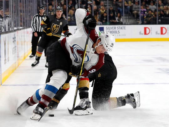 Colorado Avalanche right wing Mikko Rantanen (96) fights for the puck with Vegas Golden Knights defenseman Brayden McNabb (3) during the first period of an NHL hockey game, Monday, Dec. 23, 2019, in Las Vegas. (AP Photo/Steve Marcus)