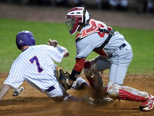 Logan Brown attempts to tag the University of Evansville's Stewart Nelson during the annual crosstown game between the city's two colleges, April 25.