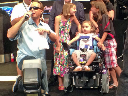 Three-year-old Ella Marini, seated, flanked by her sisters Gianna, 8, and Talia, 10, listen to Barrett-Jackson Auctions President Steve Davis announce the donation of a power wheelchair to Ella from the Darrell Gwynn Foundation.