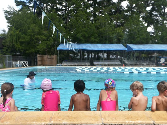 Children line the edge of the pool at Maclay School,