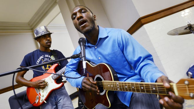 Cedric Burnside belts out the blues along with bandmate Trenton Ayres, left, during a performance inside the Capitol in Jackson.