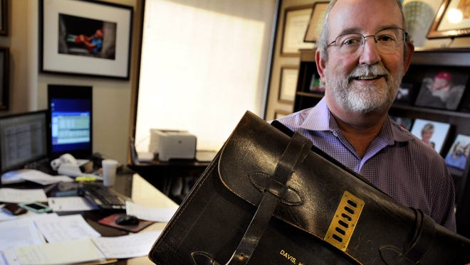Russell Guthrie, a Certified Public Accountant at Davis Kinard & Co., holds one of the original embossed leather bags Nov. 22, which was commissioned by the business when it merged in 1971 into its present form.