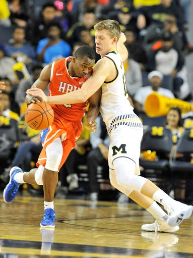 Michigan's Moritz Wagner, right, defends and is called