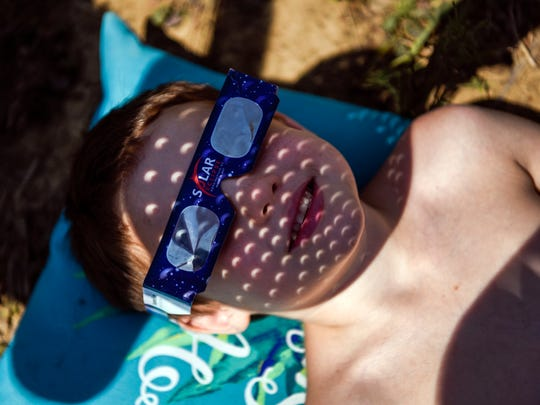Robert Glynn, 6, looks at the solar eclipse as his