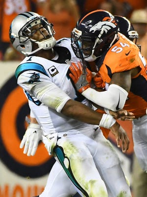 Denver Broncos inside linebacker Brandon Marshall (54) collides with Carolina Panthers quarterback Cam Newton (1) in the third quarter at Sports Authority Field at Mile High.