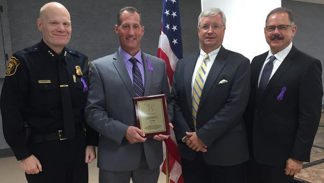 """Lt. Jon Haupt of the Farmington Hills Police Department was recognized by the Farmington/Farmington Hills Call to Action Coalition at the 28th annual Community Breakfast at the Costick Center. Haupt received recognition for his """"tireless leadership in the field of domestic violence awareness and prevention, which included the co-founding of the Farmington Hills High Risk Response Team."""" Pictured are (from left) Farmington Hills Assistant Police Chief Matt Koehn, Haupt, Farmington/Farmington Hills Call to Action Coalition chairman Mitch Seelye and Farmington Hills Police Chief Chuck Nebus."""