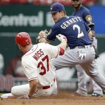 Brandon Moss of the St. Louis Cardinals is safe at second for a double as Milwaukee Brewers second baseman Scooter Gennett covers during the second inning Saturday in St. Louis.