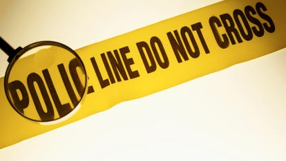 Close-up of magnifying glass highlighting text on police tape