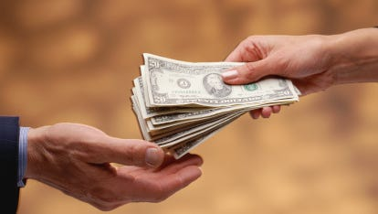 Woman's hand giving stack of US 0 bills to man's hand