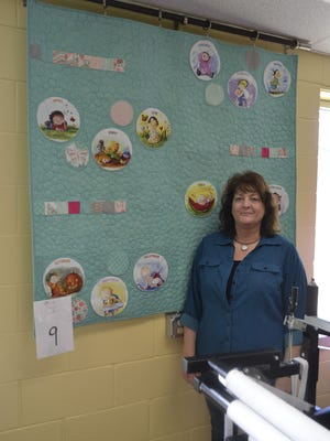 Lynn Konitzer, a quilting instructor at Northeast Wisconsin Technical College, stands in front of one of two quilts she made for the Green Bay chapter of Project Linus' baby quilt challenge.