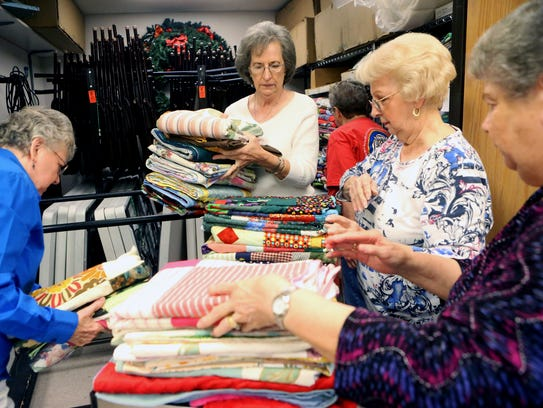 Church members from the Peace by Piece Quilters prepare