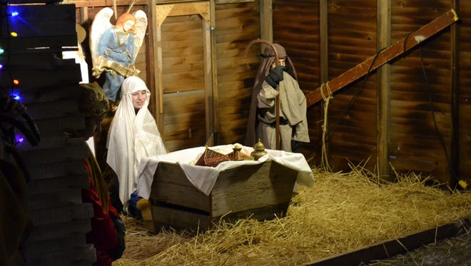 Mary, portrayed by 13-year-old Maren Parks of Green Bay, kneels behind the manger to keep watch over baby Jesus in a stable during one of three Live Nativity Worship services held outside Our Saviour Lutheran Church in Green Bay on Wednesday night, Dec. 17. The annual Christmas event included seventh- and eighth-grade confirmation students from the church recreating The Nativity in Bethlehem.