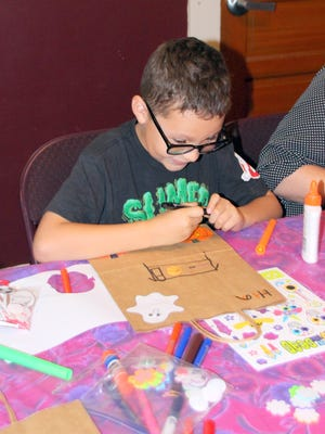 On Saturday at the Silver City Museum, kids arrived to create a Halloween trick-or-treat bag. Dakota Morales, 7, works carefully on his bag.