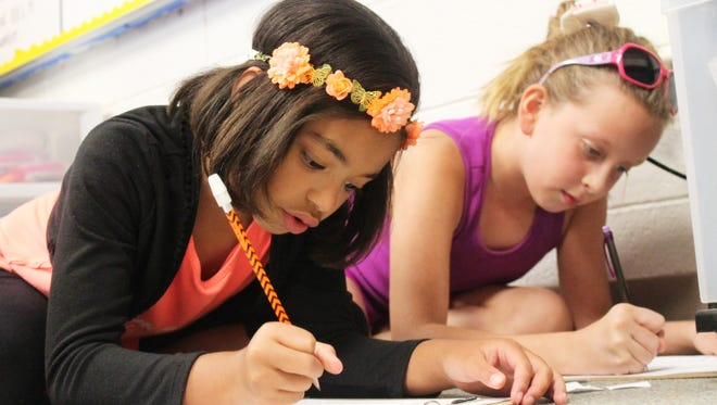 In this Daily News file photo, Kaydence Reisner and Amber Sims focus on their classwork.