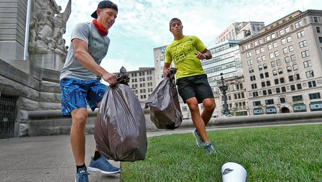 "Casey Seaton, left, and Jason Shaw, with the November Project Indy, demonstrate plogging on Monument Circle, Friday, July 6, 2018.  The November Project and Keep Indianapolis Beautiful have come together to host the ""Summer of Plogging Series,"" using a eco-friendly workout craze, plogging, which combines jogging and picking up trash, for a monthly six-kilometer plog during the summer."