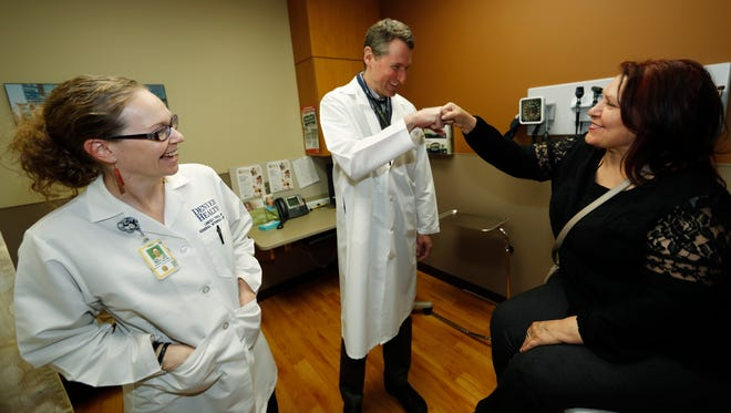 Dr. Michael Russum, center, congratulates patient Ruby Giron after her checkup as Dr. Lindsey Fish, left, looks on in Denver Health Medical Center's primary care clinic located in a low-income neighborhood in southwest Denver. A proposed health care overhaul moving through the U.S. Congress in March 2017 would have dramatic effects in Colorado, which was one of 31 states to make it easier to qualify for Medicaid, government-covered health insurance for the needy. (AP Photo/David Zalubowski, File)