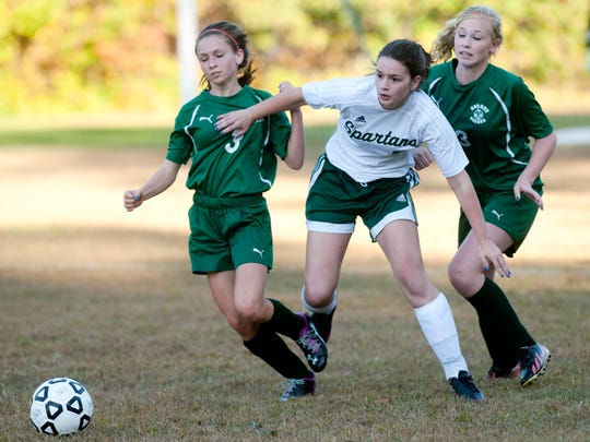 Winooski's Nathalie Bray, center, chases for the ball alongside Enosburg's Ali Gervais and Olivia Lombard during a game last year.