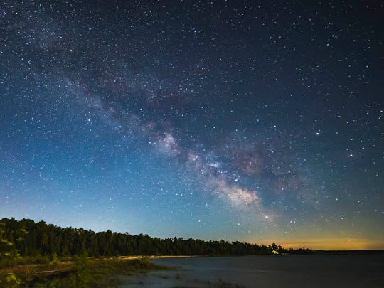 The Milky Way is visible in the night sky over Headlands